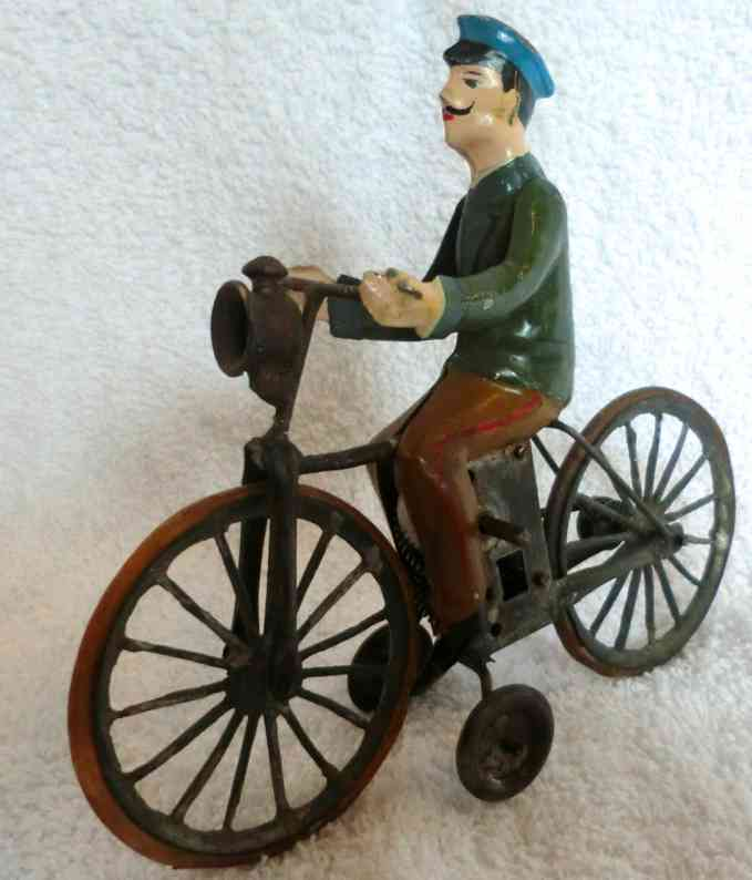 carette tin toy man on bike with clockwork