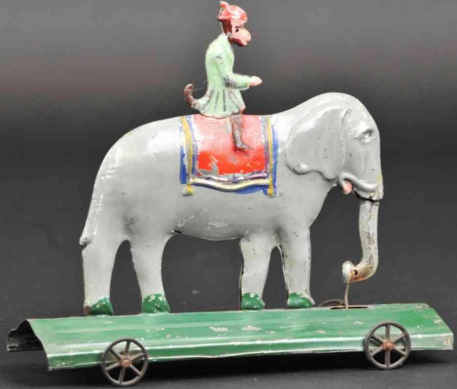 fallows blech spielzeug affe reitet auf elefanten