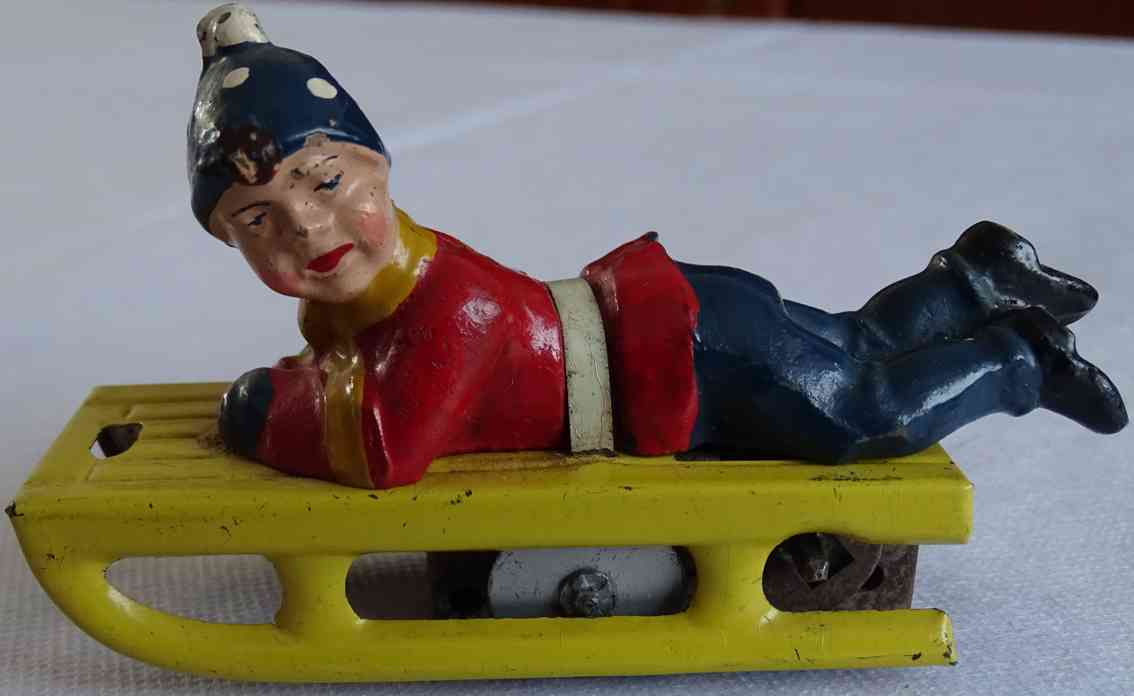 gescha tin toy boy on yellow sled with clockwork