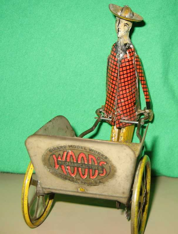girard tin toy porter in red checked jacket pushing a three sided cart with