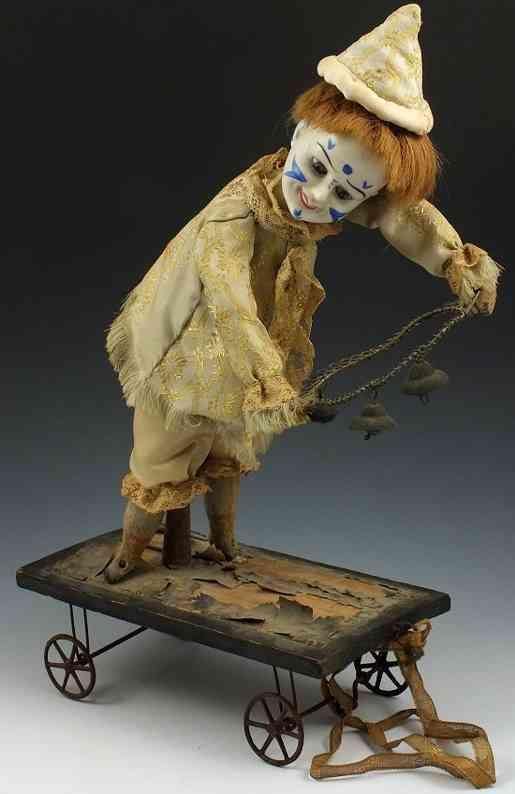 unknown blech spielzeug clown clown mit porzellankopf und papieraugen auf karre; der clown