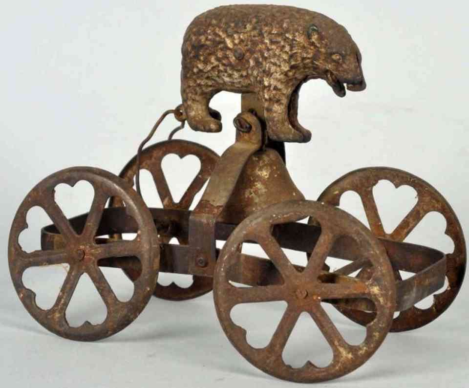 Cast iron bear as bell toy with tin heart-shaped wheels