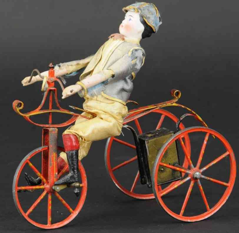 unknown boy on tricycle tin toy boy riding mechanical tricycle, made in france,  a very earl