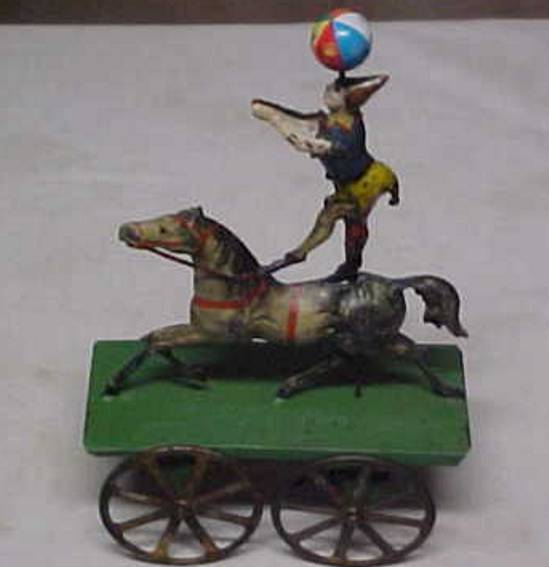 Clown standing on a horse riding on a wagon