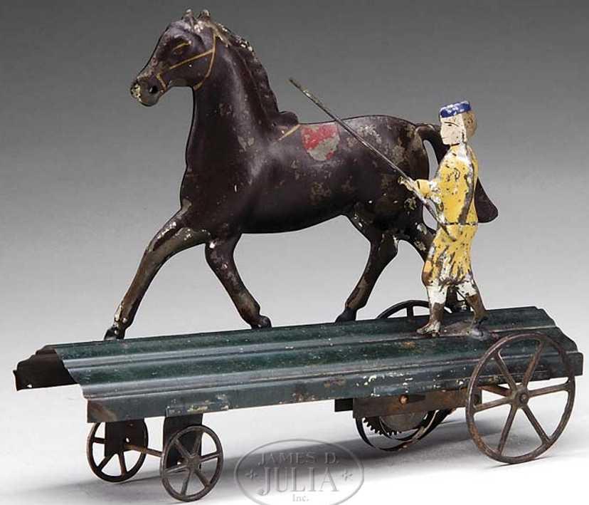 Fallows Pferd mit Trainer auf Blechplattform mit Uhrwerk