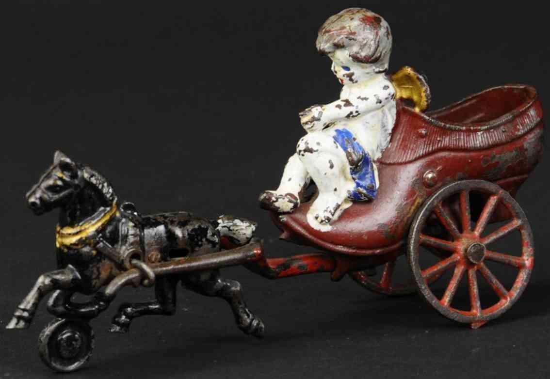 kenton hardware co cast iron toy cupid on horse drawn shoe
