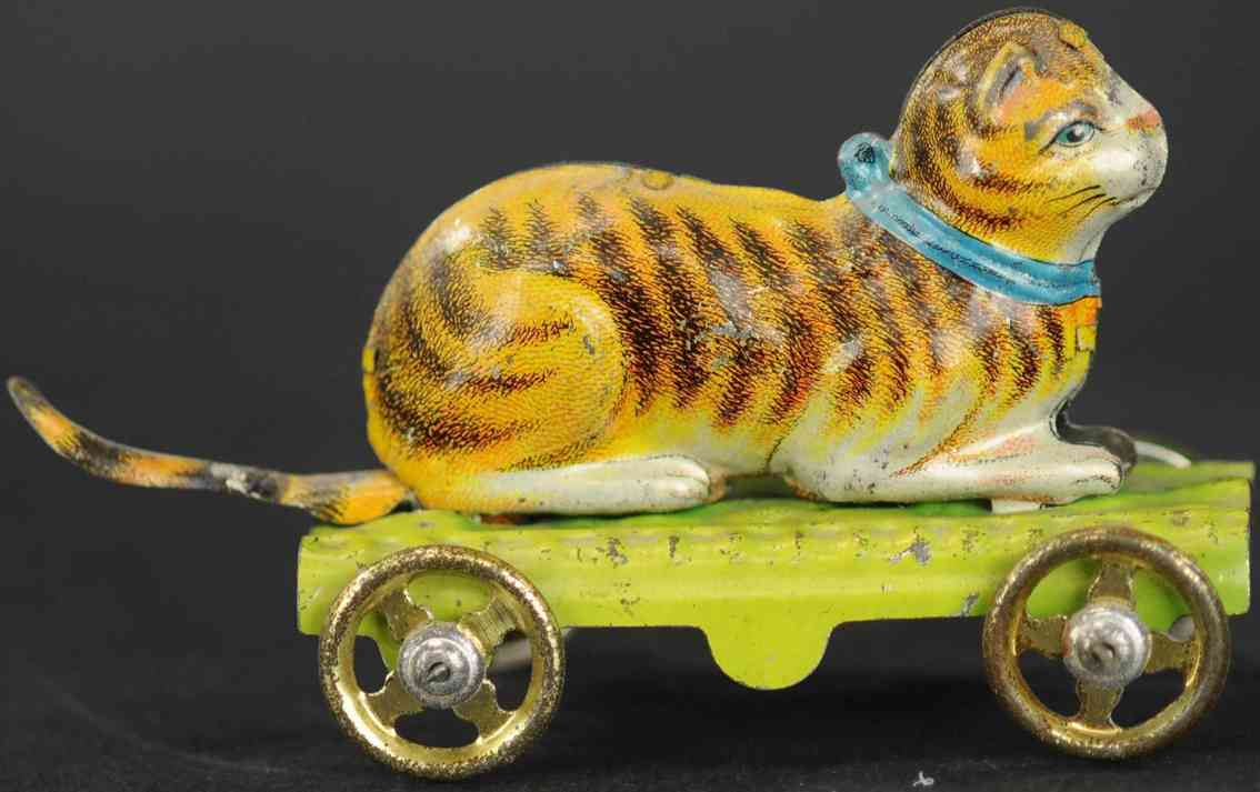 fischer georg penny toy cat sitting on green platform with gold spoke wheels