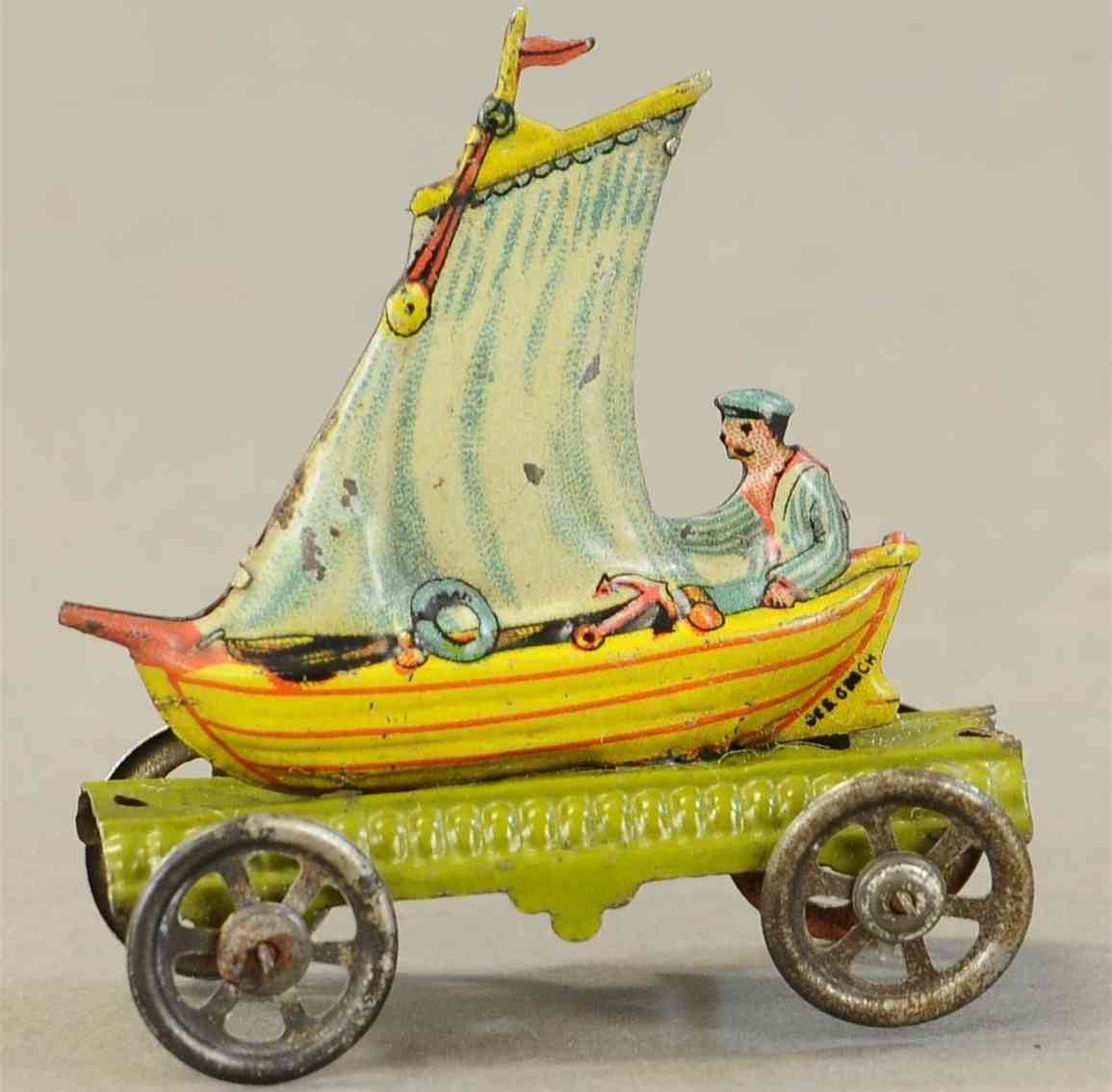 meier penny toy man in sailboat on green platform with spoked wheels