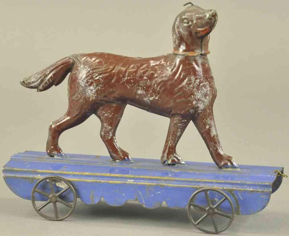 fallows blech spielzeug brauner hund mit gelenken auf blauer plattform
